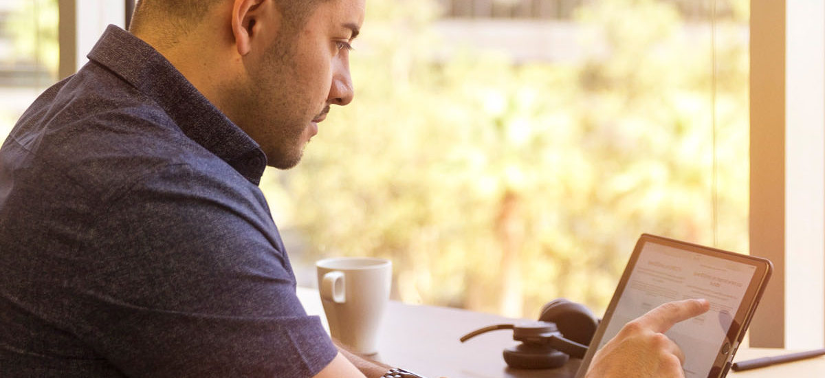 man sitting in restaurant tapping on tablet