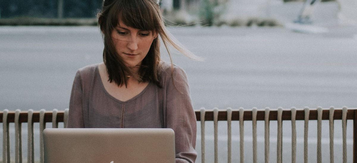 Woman sitting in windy street working on laptop