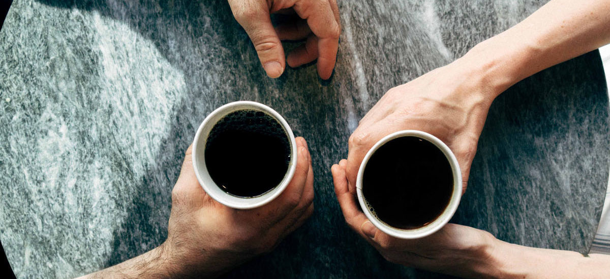 coffee cups from the top with hands holding them