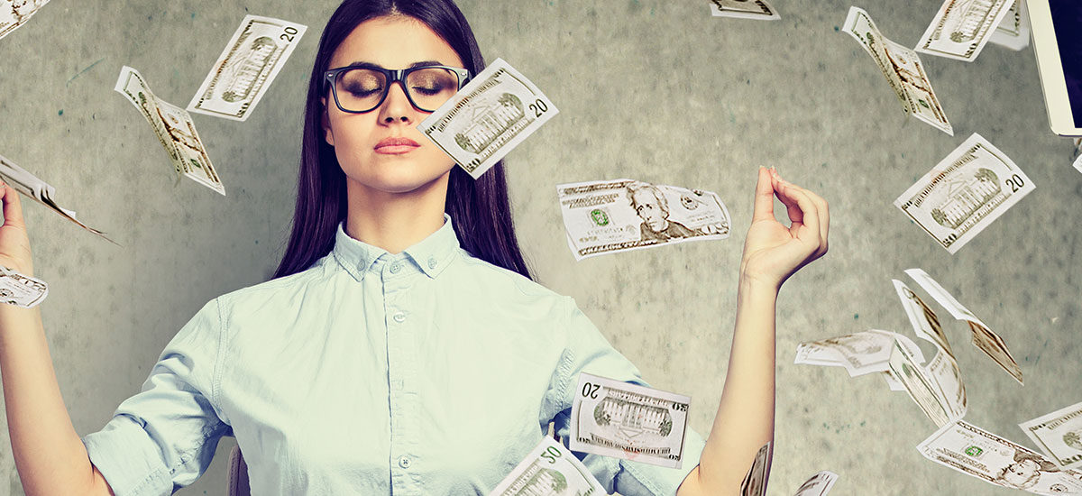 Woman meditating with money all around her