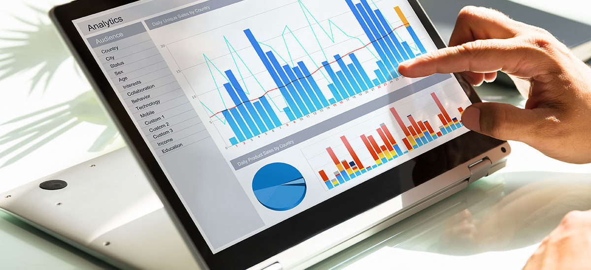Businessman's hands using a tablet with graphs