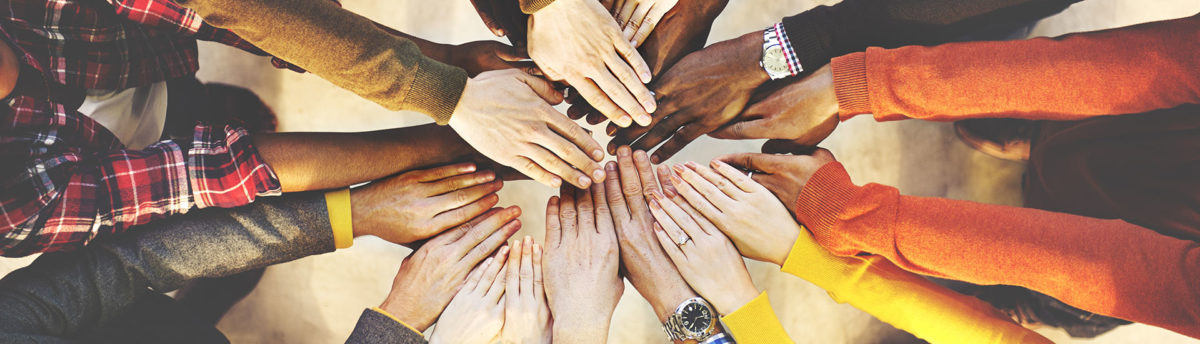 Diverse group of people standing in a circle reaching their hands into the middle