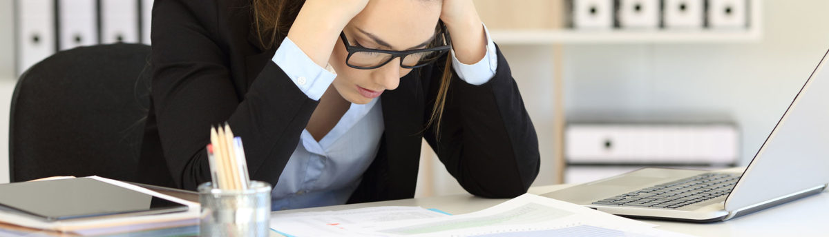 Worried looking woman holding her head reading a document at her desk