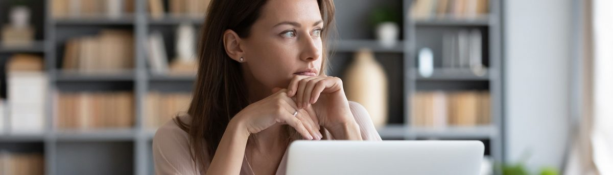 Pensive young woman planning and thinking in front of laptop
